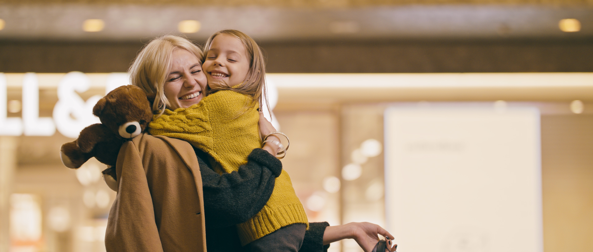 mother and daughter with teddy bear at iulius town timisoara on christmas popotam productions video agency after color grading