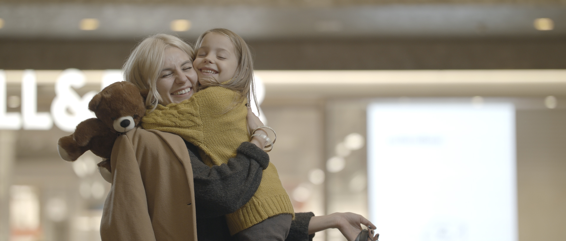 mother and daughter with teddy bear at iulius town timisoara on christmas popotam productions video agency before color grading